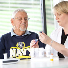 A nurse instructs an older Navy Vet on his medications