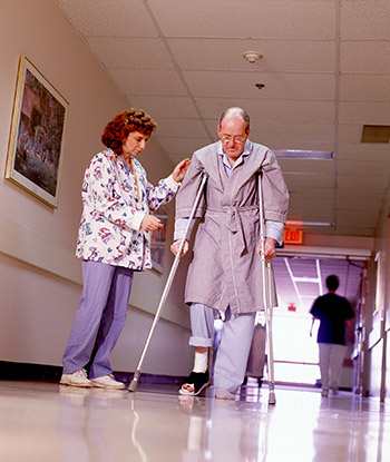 Nurse helps patient on crutches in hospital.