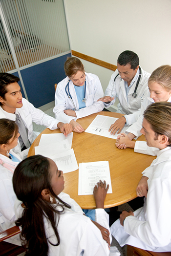 Health care professionals meet around a table